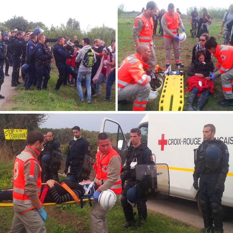 Isabelle évacuée par la Croix Rouge sous les regards gênés des gendarmes, jambe cassée par un coup de pied du gendarme fou et visage brûlé par les lacrymos à bout portant (matricule relevé, plainte en cours)